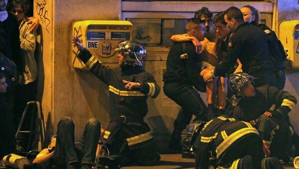 French fire brigade members aid an injured individual near the Bataclan concert hall following fatal shootings in Paris, France, November 13, 2015 - Sputnik International