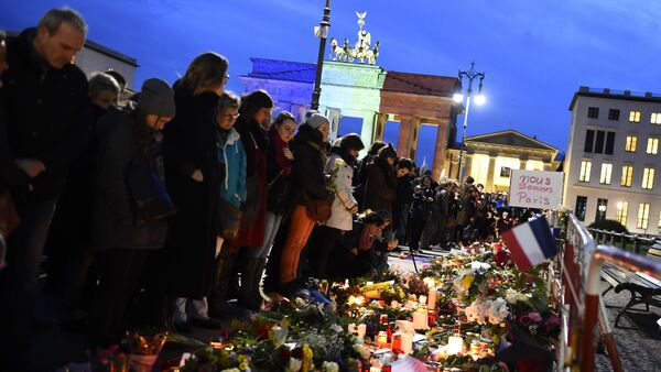 A banner reading 'We are Paris ' is pictured among candles and flowers in front of the Brandenbourg Gate outside the French embassy in Berlin, on November 14, 2015 a day after deadly attacks in Paris - Sputnik International