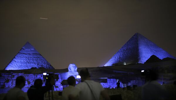 Egyptians watch the historical site of the Giza Pyramids as they are illuminated with blue light, as part of the celebration of the 70th anniversary of the United Nations, in Giza, just outside Cairo, Egypt, Saturday, Oct. 24, 2015 - Sputnik International