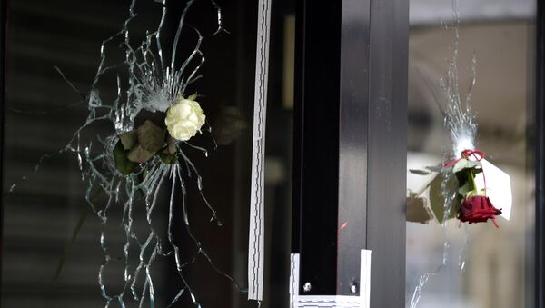 Roses are placed in bullet holes of the window of a Japanese restaurant along the Rue de Charonne in central east Paris, on November 15, 2015, two days after deadly attacks across the city - Sputnik International