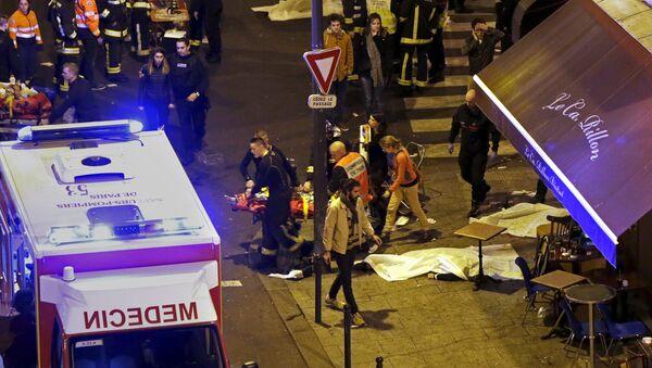 French fire brigade members aid an injured individual near the Bataclan concert hall following fatal shootings in Paris, France, November 13, 2015. - Sputnik International
