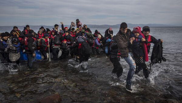 Migrants and refugees disembark safely from a dinghy at a beach on the Greek island of Lesbos after crossing the Aegean sea from the Turkish coast, Monday, Nov. 16, 2015 - Sputnik International