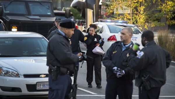 A security guard (C) is escorted out of a building on 19th and K Street NW in Washington, DC, November 16, 2015, by DC Metropolitan Police during a barricade situation - Sputnik International