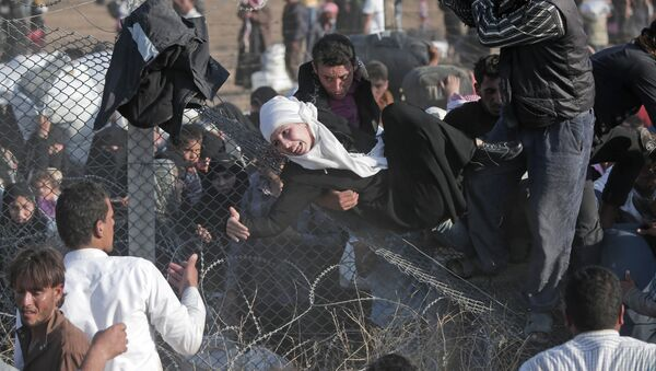 FILE - In this Sunday, June 14, 2015 file photo, Syrian refugees are helped into Turkey after breaking the border fence and crossing from Syria in Akcakale, Sanliurfa province, southeastern Turkey - Sputnik International