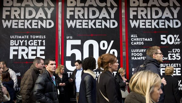 Shoppers are pictured walking past 'Black Friday' advertising in shop windows on Oxford Street in central London on November 28, 2014. - Sputnik International