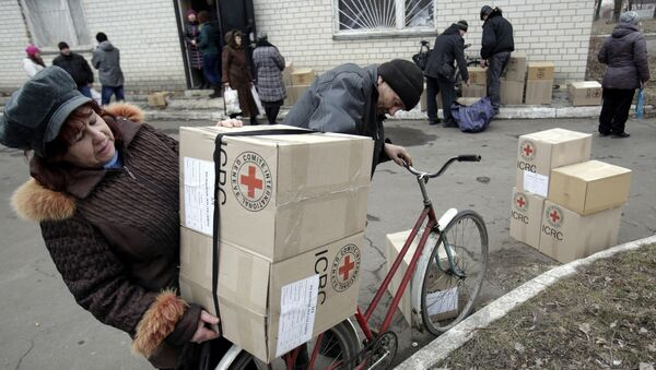File photo of the residents of the eastern Ukrainian city of Avdiivka, in the Donetsk region controlled by Ukrainian forces, carry boxes containing Red Cross humanitarian aid in Avdiivka on March 2, 2015 - Sputnik International