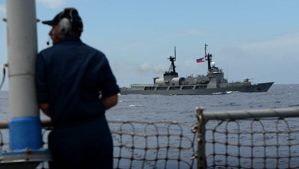 US Navy personnel looks at Philippine Navy vessel BRP Ramon Alcaraz during the bilateral maritime exercise between the Philippine Navy and US Navy dubbed Cooperation Afloat Readiness and Training (CARAT 2014) aboard the USS John S. McCain in the South China Sea near waters claimed by Beijing on June 28, 2014 - Sputnik International