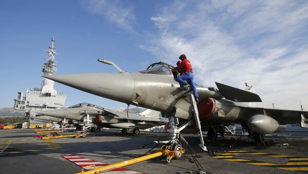 Flight deck crew work on Rafale fighter jets aboard the French nuclear-powered aircraft carrier Charles de Gaulle before its departure from the naval base of Toulon, France, November 18, 2015 - Sputnik International