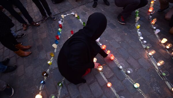 A person lights a candle during a candle light vigil to the victims of the Paris attacks in Brussels' Molenbeek district, on November 18, 2015. - Sputnik International