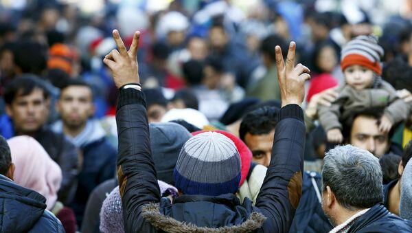 Migrants gesture after arriving at the Austrian-German border in Achleiten - Sputnik International