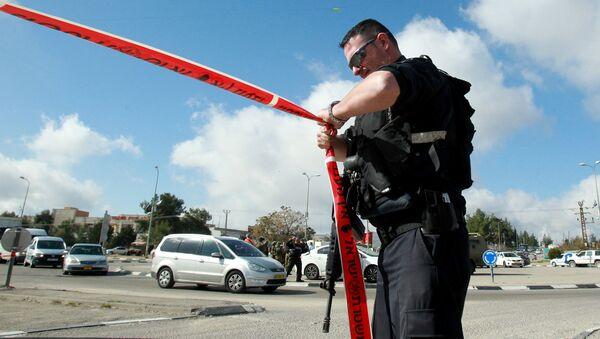 An Israeli police officer holds police tape. - Sputnik International