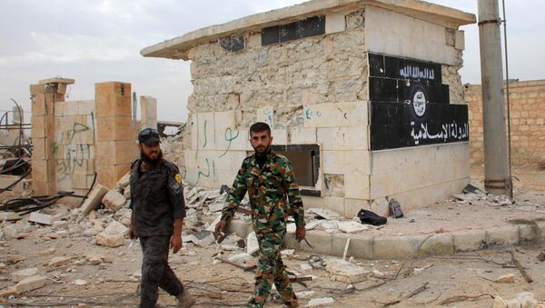 Syrian government forces walk past a building bearing an image on the wall with Islamic writing and reading in Arabic the Islamic State in the village of Jabboul on the eastern outskirts of the northern Syrian city of Aleppo after taking control of the village from Islamic State (IS) group islamists on October 24, 2015 - Sputnik International