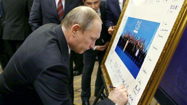 Russian President Vladimir Putin signs a print of the G20-Turkey family photo at the Group of 20 (G20) summit, in the Mediterranean resort city of Antalya, on November 15, 2015 - Sputnik International
