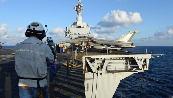 French navy technicians work near a French Rafale aircraft on the flight deck on the aircraft carrier Charles-de-Gaulle, in eastern Mediterranean sea, on November 21, 2015 - Sputnik International