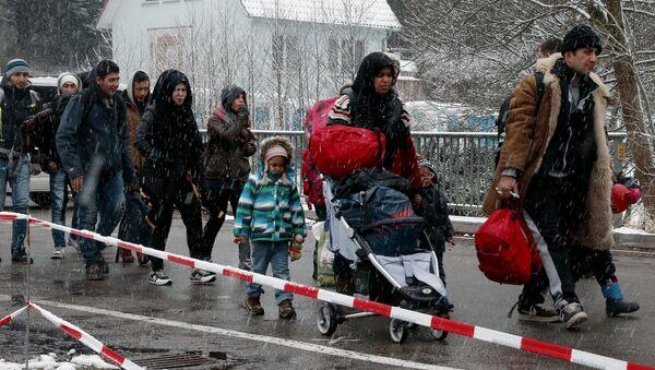 Migrants stay in queue during heavy snowfall before passing Austrian-German border in Wegscheid in Austria, near Passau November 22, 2015 - Sputnik International
