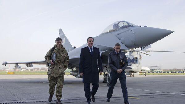 Britain's Prime Minister David Cameron (C) walks with Group Captain David Manning (R) past an RAF Eurofighter Typhoon fighter jet during his visit to Royal Air Force station RAF Northolt in London, Britain November 23, 2015 - Sputnik International
