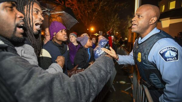 A police officer talks with demonstrators in front of a north Minneapolis police precinct during a protest in response to the shooting death of Jamar Clark by police officers in Minneapolis, Minnesota, November 18, 2015 - Sputnik International