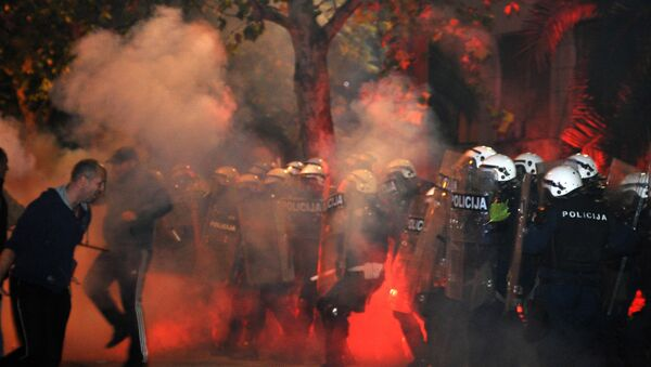 Montenegrin police officers are engulfed in smoke and flames as opposition supporters hurled torches on them during a protest in front of the Parliament building in Podgorica, Montenegro Saturday, Oct. 24, 2015. Police fired tear gas at opposition supporters who hurled fire bombs and torches to demand the resignation Prime Minister Milo Djukanovic's government which hopes to steer the Balkan country toward NATO membership later this year - Sputnik International