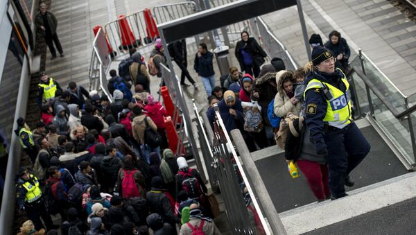 Police organize the line of refugees at on the stairway leading up from the trains arriving from Denmark at the Hyllie train station outside Malmo, Sweden, November 19, 2015. - Sputnik International