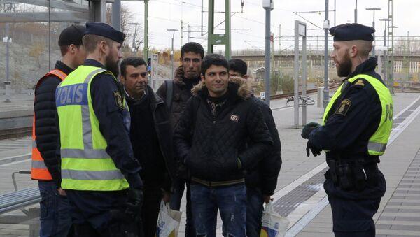 Swedish police officers speak to a group of people at the Hyllie train station near Malmo, Sweden, November 12, 2015. - Sputnik International