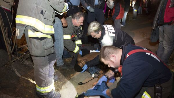 In this Nov. 23, 2015 photo, emergency responders aide one of five protesters shot near the site of an ongoing protest over the fatal shooting of a black man by a police officer in Minneapolis. Police, who haven't commented on a motive for the attack on the protesters, said three people were in custody. The injuries were not-life threatening. - Sputnik International