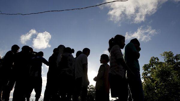 People stand near at a crime scene where seven men were killed, in Tegucigalpa, Honduras - Sputnik International