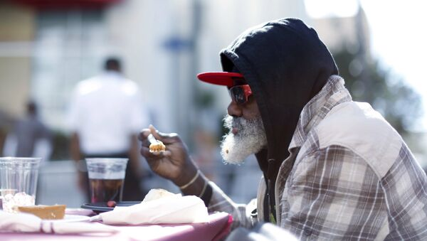 A man eats an early Thanksgiving meal served to the homeless. - Sputnik International