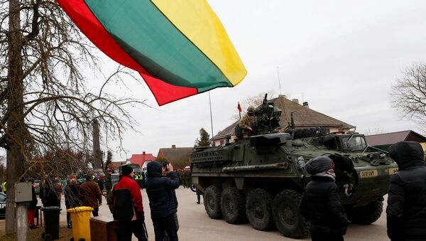 Local residents watch as a members of US Army's 2nd Cavalry Regiment ride on an armored vehicle during the ''Dragoon Ride'' military exercise, in Salociai some 178 kms (110 miles) north of the capital Vilnius, Lithuania, Monday, March 23, 2015. - Sputnik International