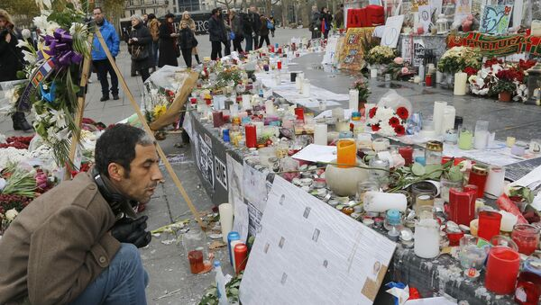 """A man reads messages at the Place de la Republique in Paris, Friday, Nov. 27, 2015. A subdued France paid homage Friday to those killed two weeks ago in the attacks that gripped Paris in fear and mourning, honoring each of the 130 dead by name as the president pledged to """"destroy the army of fanatics"""" who claimed so many young lives. - Sputnik International"""