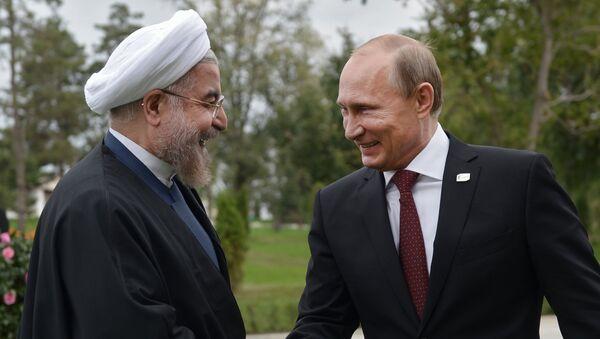 Iranian President Hassan Rouhani (L) shakes hands with his Russian counterpart Vladimir Putin - Sputnik International