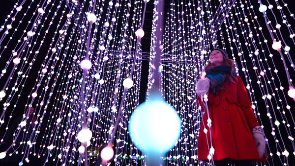 A woman poses for pictures in a light display during a photocall at Kew Gardens in south west London, on November 24, 2015, during their launch of the Christmas at Kew Gardens event - Sputnik International