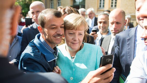 Asylum seeker (C, L) takes a selfie picture with German Chancellor Angela Merkel (C, R) following Merkel's visit at a branch of the Federal Office for Migration and Refugees and a camp for asylum-seekers in Berlin on September 10, 2015 - Sputnik International