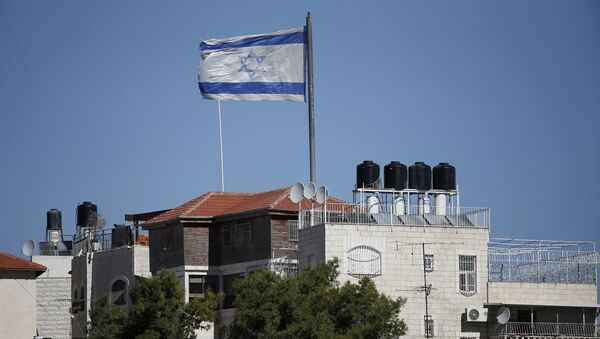 A giant Israeli flag flies over a settlement building situated in the middle of a Palestinian neighbourhood of Al-Tur in East Jerusalem, on November 11, 2014 - Sputnik International