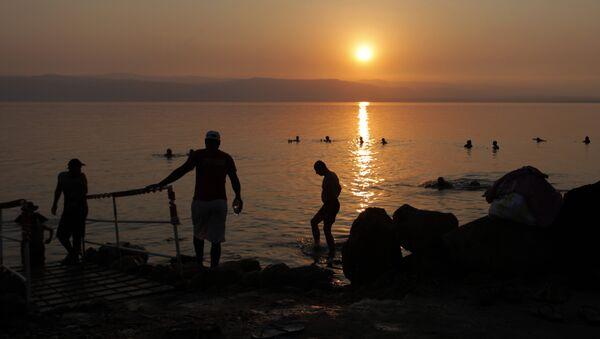 Tourists and local residents visit the Dead Sea beach, 34 miles (55 kilometers) southeast of Amman, Jordan, Friday, June 29, 2012 - Sputnik International