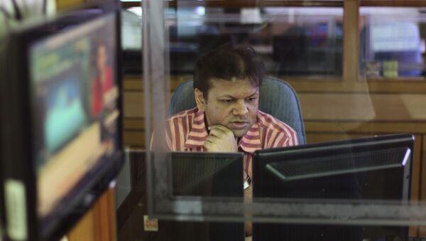 An Indian stockbroker looks at a trading terminal at a stock brokerage in Mumbai, India, Thursday, Aug. 22, 2013 - Sputnik International