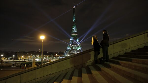 A couple stand on the stairs as an artwork entitled 'One Heart One Tree' by artist Naziha Mestaoui is displayed on the Eiffel tower as part of the COP21, United Nations Climate Change Conference. - Sputnik International