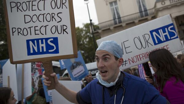A protester holds a placard at a demonstration in support of junior doctors in London, in this file photograph dated October 17, 2015 - Sputnik International