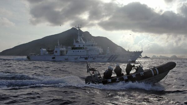 In this Sunday, Aug. 18, 2013 file photo, Japanese Coast Guard boat and vessel sail alongside Japanese activists' fishing boat, not in photo, warning the activists away from a group of disputed islands called Diaoyu by China and Senkaku by Japan - Sputnik International
