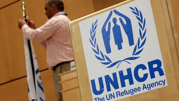 A staff installs a UNHCR flag close to a logo of UN High Commissioner for Refugees (UNHCR) prior to the opening of a two-day United Nations conference trying to boost support for Iraqis who have fled violence, 17 April 2007 at the UN Office in Geneva - Sputnik International