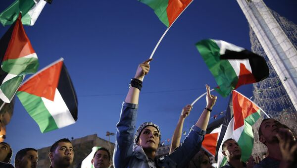 Palestinians wave their national flags as they watch a live-screening of president Mahmud Abbas' speech followed by the raising of the Palestinian flag at the United Nations headquarters in New York, on September 30, 2015 in the city of Ramallah - Sputnik International