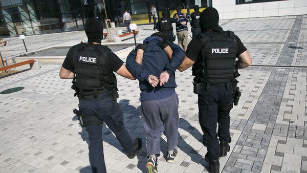 Kosovo police officers escort unidentified Kosovo Albanian men who are suspects in a terror plot, to a court in Kosovo's capital Pristina, Sunday, July 12, 2015 - Sputnik International