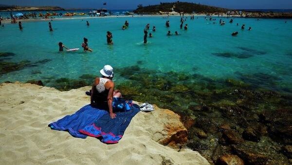 A woman sit on the sand as other people enjoy the sea at Nissi Beach in the famous southeastern coastal resort of Ayia Napa, Cyprus, Saturday, June 14, 2014 - Sputnik International