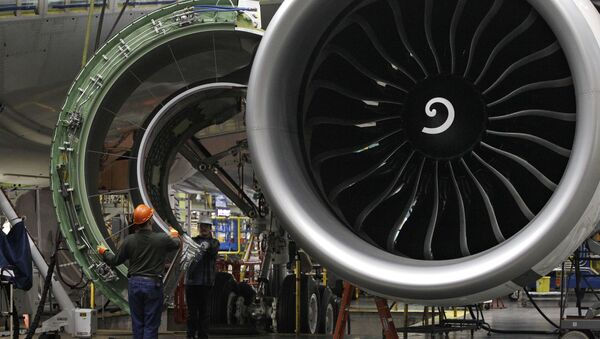 Worker maneuver the cover of a engine into place on a Boeing 777 jet at the company's manufacturing plant, Monday, Feb. 14, 2011, in Everett, Wash. - Sputnik International