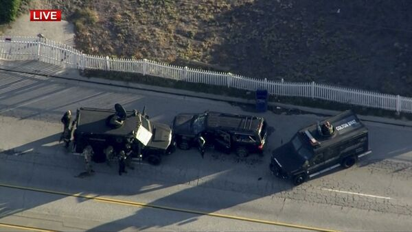 Police armored cars close in on a suspect vehicle following a shooting incident in San Bernardino. - Sputnik International