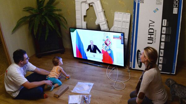 A young family in Vladivostok watches the live broadcast of Russian President Vladimir Putin's Presidential Address to the Federal Assembly - Sputnik International