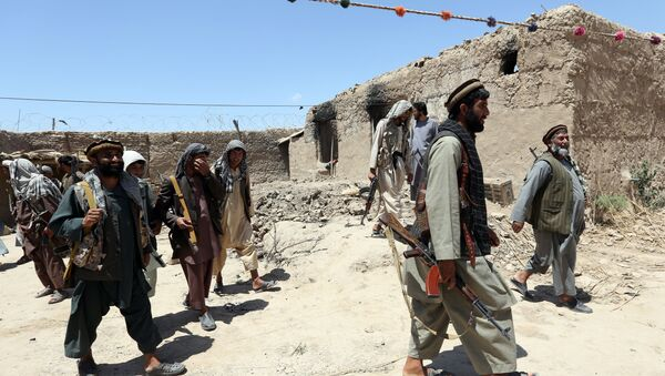 In this Thursday, May 21, 2015 file photo, local militia group fighters walk past a building torched by Taliban fighters at Talawka village in Kunduz province, north of Kabul, Afghanistan - Sputnik International