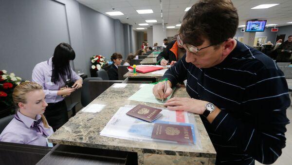 A visitor files papers at Visa Application Center - Sputnik International