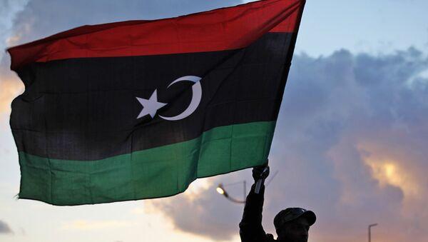 A Libyan waves the national flag - Sputnik International