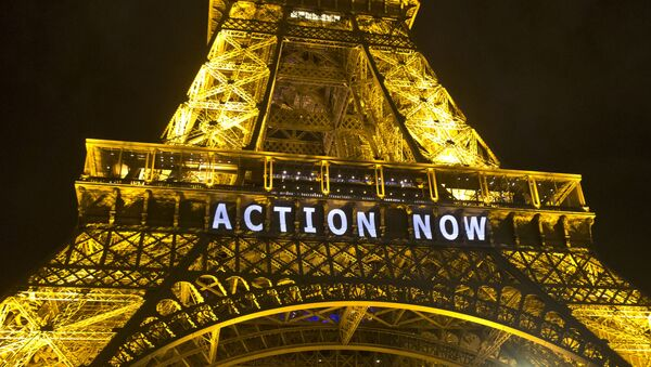 The Eiffel Tower lights up with the sloganAction Nowreferring to the COP21, United Nations Climate Change Conference in Paris, Sunday, Dec. 6, 2015 - Sputnik International