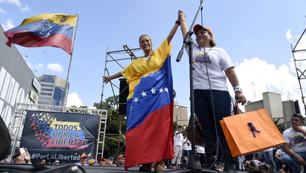 Lilian Tintori (L), wife of jailed Venezuelan opposition leader Leopoldo Lopez, holds up the hand of a supporter during a rally in Caracas - Sputnik International